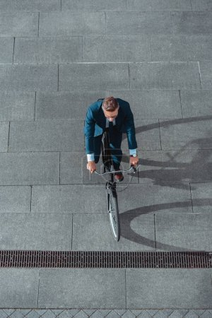 Photo for High angle view of businessman in formal wear riding bicycle on street - Royalty Free Image