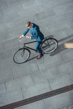 Foto de Vista de ángulo alto de empresario en ropa formal, montar en bicicleta y controlando el reloj de pulsera - Imagen libre de derechos