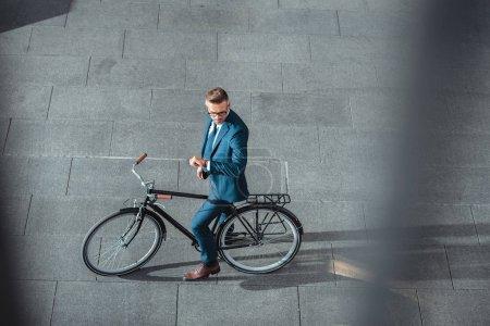 vista de ángulo alto de hombre de negocios en el desgaste formal sentado en bicicleta y comprobar reloj de pulsera