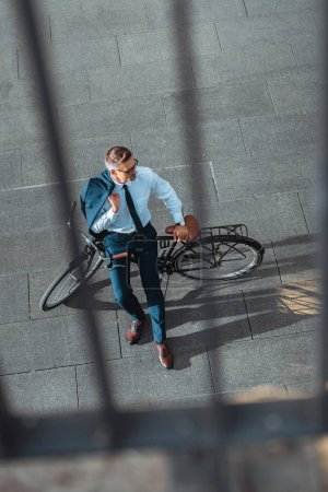 high angle view of middle aged businessman holding suit jacket and looking away while sitting on bicycle