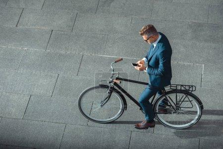 Photo pour Vue d'angle élevé d'homme d'affaires en tenues à l'aide de smartphone en se tenant debout avec la bicyclette sur la rue - image libre de droit