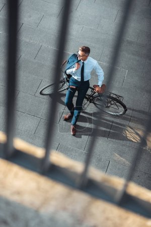 Photo for Selective focus of businessman holding suit jacket and sitting on bike - Royalty Free Image