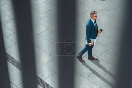 Photo for High angle view of businessman with coffee to go and newspaper walking on street - Royalty Free Image