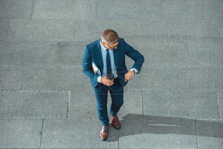 exitoso hombre de negocios de mediana edad sosteniendo café para ir y comprobar reloj de pulsera en la calle