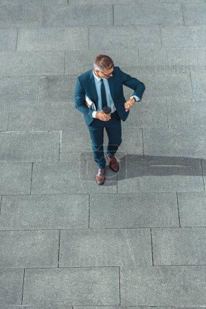 vista de ángulo alto del exitoso hombre de negocios de mediana edad sosteniendo café para ir y comprobar el reloj de pulsera en la calle