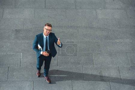 Photo pour Un angle élevé Découvre d'homme d'affaires heureux holding tasse de papier et montrant le pouce vers le haut sur la rue - image libre de droit