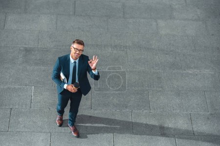 high angle view of happy businessman holding paper cup and showing ok sign on street