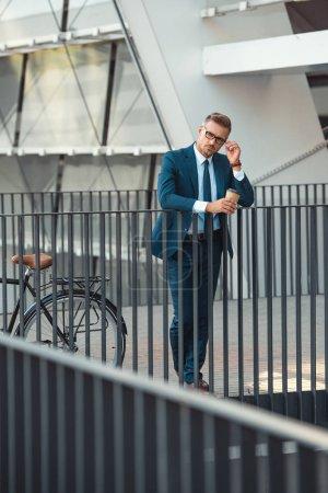 Photo pour Homme d'affaires en tenues tenant café pour aller et réglage de lunettes en se tenant debout près de vélo sur la rue - image libre de droit