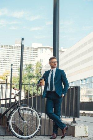 Foto de Hombre de negocios guapo sosteniendo café para llevar y mirar lejos estando cerca de bicicleta en la calle - Imagen libre de derechos