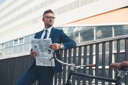 Photo for Businessman in suit and eyeglasses holding newspaper and looking away while standing with bike on street - Royalty Free Image