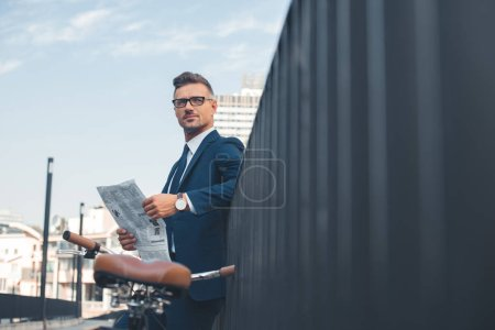 handsome buisnessman in suit and eyeglasses holding newspaper while standing with bike on street