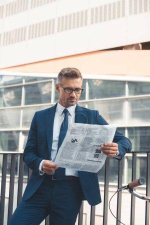 Photo pour Beau milieu busnessman âgé en costume et lunettes de lecture de journal sur la rue - image libre de droit