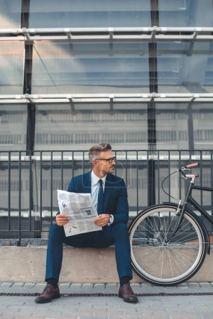 Photo for Middle aged businessman holding newspaper and looking away while sitting near bicycle on street - Royalty Free Image