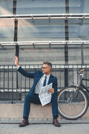 middle aged businessman holding newspaper and waving hand while sitting near bicycle on street