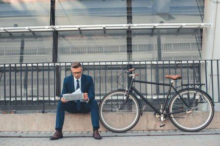 Photo pour Homme d'affaires d'âge moyen lisant un journal assis près du vélo dans la rue - image libre de droit