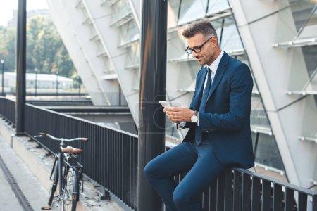 Photo pour Souriant middle âgés homme d'affaires de lunettes à l'aide de smartphone tout en étant assis sur la rue - image libre de droit