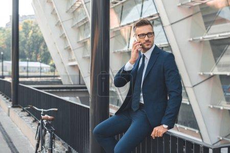Photo pour Bel homme d'affaires en costume et lunettes parlant par smartphone et regardant loin tout en étant assis sur la rue - image libre de droit