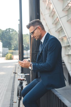 Photo for Side view of businessman in suit and eyeglasses using smartphone on street - Royalty Free Image