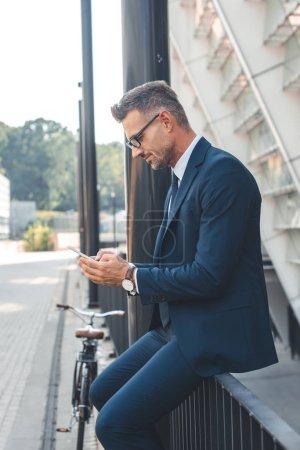 Photo pour Vue latérale de l'homme d'affaires en costume et lunettes de vue à l'aide de smartphone sur rue - image libre de droit