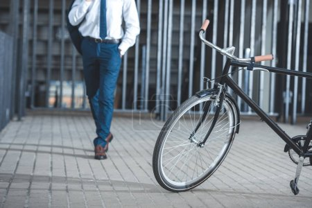 cropped shot of businessman holding suit jacket and going to bicycle parked on street