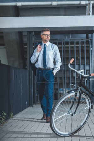 handsome businessman in eyeglasses holding suit jacket and looking away while going to bicycle parked on street