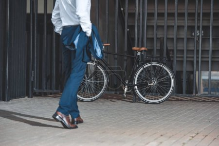 cropped shot of businessman in formal wear going to bike parked on street