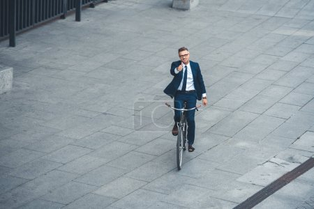 Photo for High angle view of happy middle aged businessman showing thumb up and smiling at camera while riding bicycle on street - Royalty Free Image