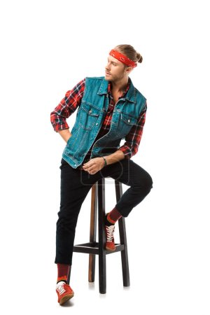 young hipster man in denim vest and red checkered shirt posing on chair isolated on white