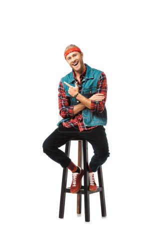laughing stylish man in denim vest and red checkered shirt pointing by finger isolated on white