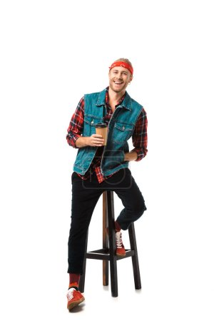 Photo for Cheerful man in headband and denim vest sitting on chair with coffee cup isolated on white - Royalty Free Image