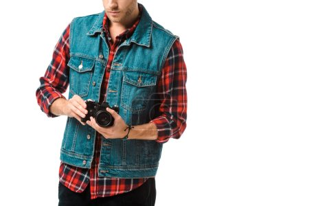 partial view of hipster male photographer in denim vest and checkered shirt shooting on camera isolated on white