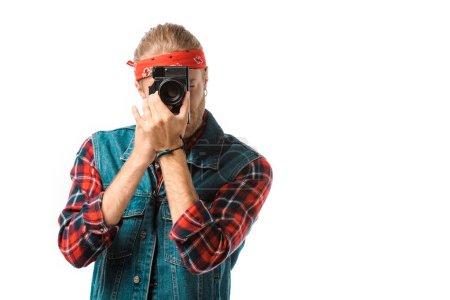 Photo pour Photographe mâle hipster concentré en veste de denim et chemise à carreaux de tir sur caméra isolé sur blanc - image libre de droit