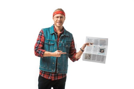 happy hipster man in denim vest pointing by finger at travel newspaper isolated on white