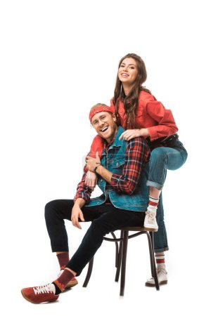 laughing stylish man sitting on chair while his hipster girl standing behind isolated on white