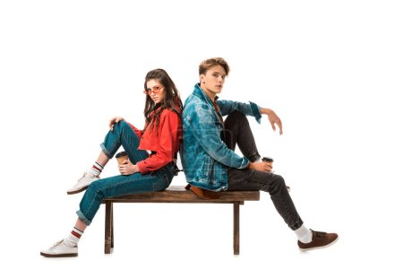 young hipster couple with paper cups of coffee sitting back to back on bench isolated on white