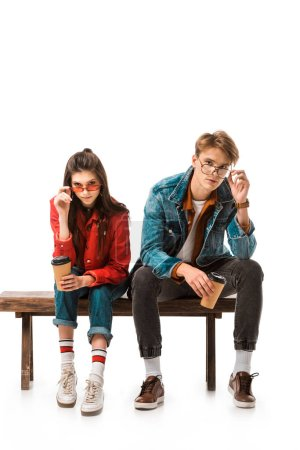 fashionable hipster couple with coffee cups adjusting eyeglasses and sitting on bench isolated on white