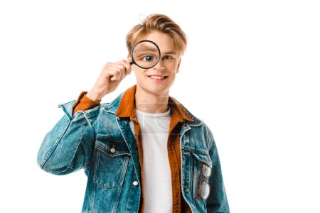 happy young hipster man in denim jacket having fun with magnifier isolated on white