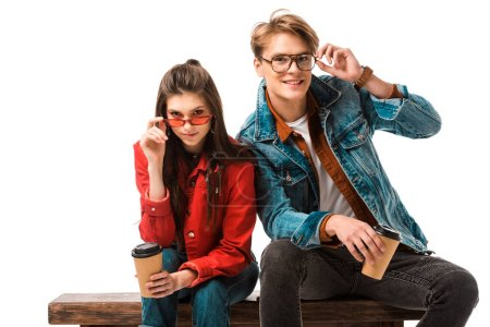happy hipster couple with coffee cups adjusting eyeglasses and sitting on bench isolated on white
