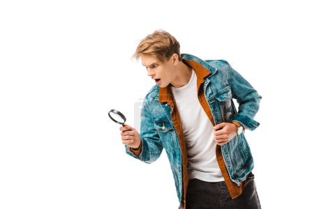 shocked young hipster man looking at magnifying glass isolated on white