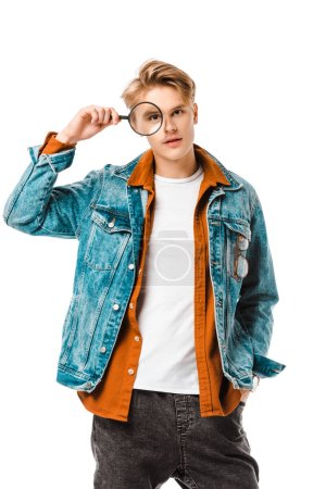 handsome young hipster man in denim jacket looking onto magnifier isolated on white