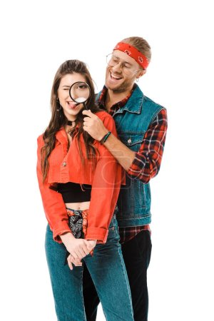 happy hipster having fun with magnifying glass while his girlfriend standing near isolated on white