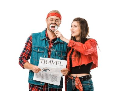 smiling young woman having fun with magnifier while her boyfriend holding travel newspaper isolated on white