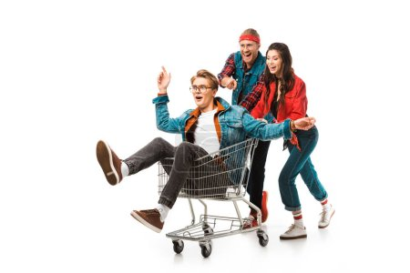 laughing stylish hipsters having fun with shopping cart isolated on white
