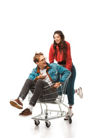 attractive hipster girl carrying shopping cart with smiling boyfriend isolated on white