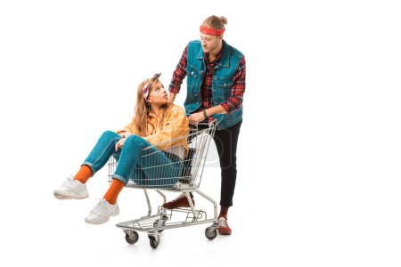 beautiful hipster girl sitting in shopping cart while her boyfriend standing behind isolated on white