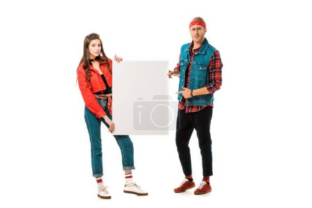young male hipster pointing at empty banner while his girlfriend standing near isolated on white