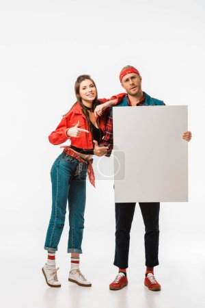 Photo for Young hipster couple pointing at empty banner isolated on white - Royalty Free Image