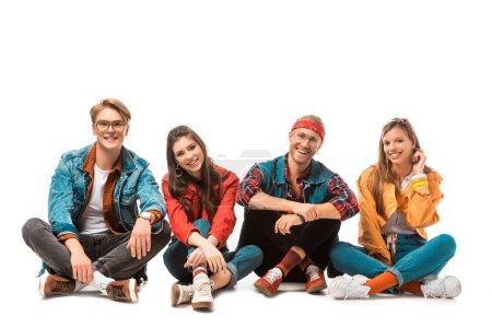 amigos hipster sonrientes sentados en el suelo y mirando a la cámara aislada en blanco