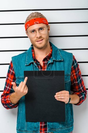 arrested hipster man in eyeglasses showing middle finger and holding empty prison board in front of police line up