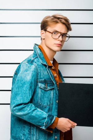 arrested hipster man in eyeglasses holding empty prison board and looking at camera in front of police line up